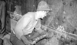 [Man adding bolts to side of ship at Burrard Drydocks]