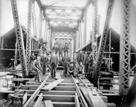 [A group of workers pose during construction of the superstructure]