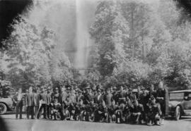 [Vancouver police officers and Pipe Band posing in front of waterfall]