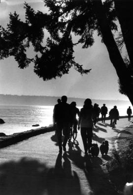 Strollers and cyclists during sunset on Stanley Park Seawall