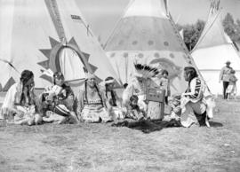 [Group of Stoney Indians listening to a radio on the Calgary Stampede grounds]