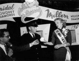 Miss P.N.E., Glenda Sjoberg, holding necklace case at Millers Jewelers display in Manufacturers b...