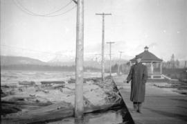 [Man standing on wooden sidewalk at shore of Kitsilano Beach during a storm]