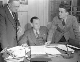 [Three men in an office at] Lawrence Manufacturing Company
