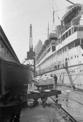 "[Sacks being hoisted onto an ""Empress"" liner at Pier B-C]"