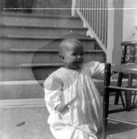 [Theodore Taylor kneeling by chair in front of house at age] 14 mo[nths]