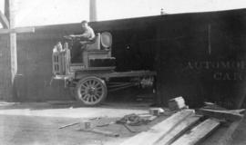 [View of man loading automobile freight car]