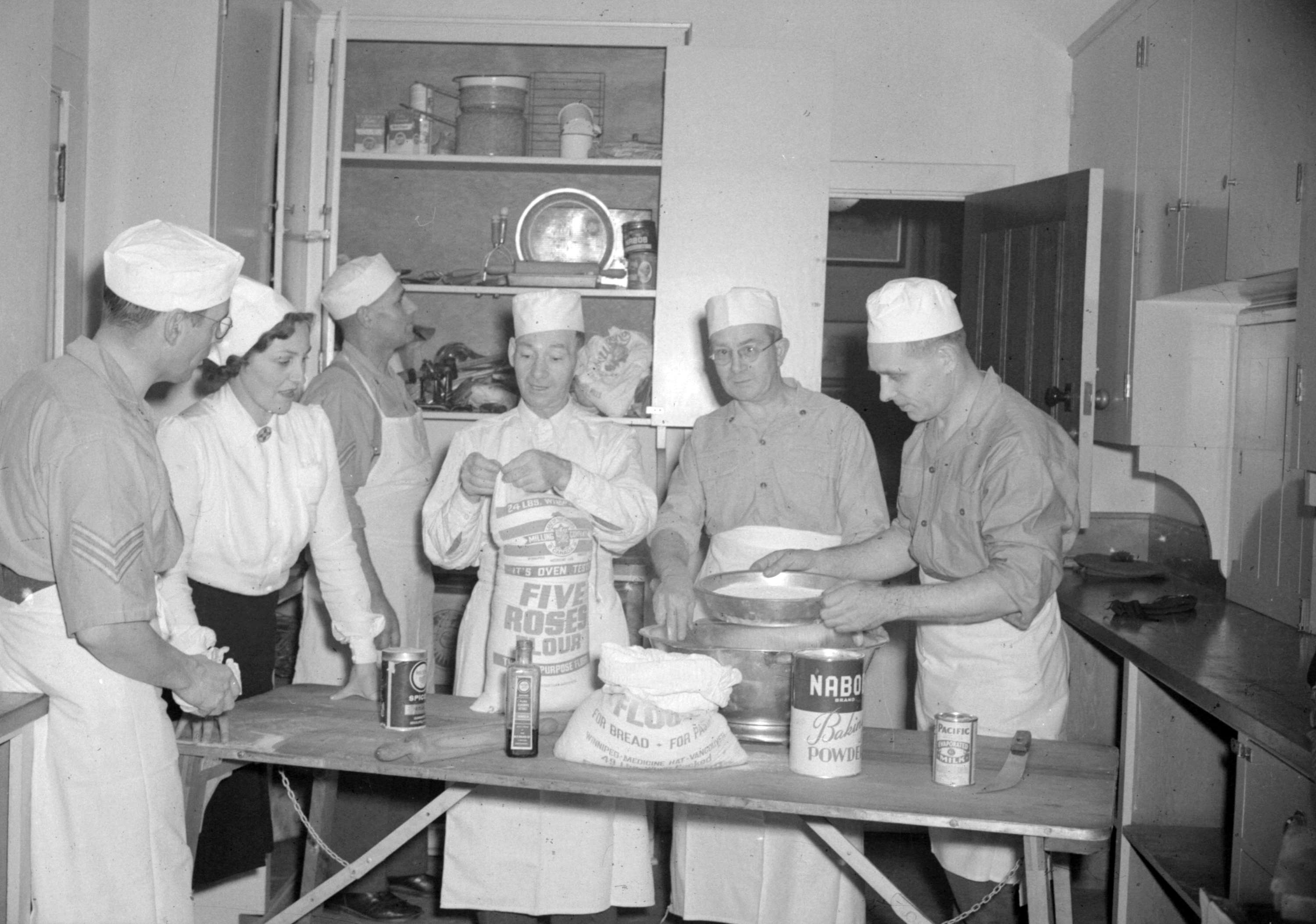 ... - [Group of people, some in military uniform, in a kitchen baking