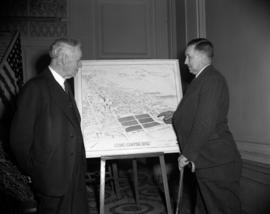 [Two men looking at a drawing for a proposed civic centre site]
