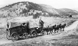 [Covered wagons leaving the Thompson River Bridge on the Lytton Lillooet Road]