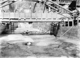 [Partially cleared area below scaffolding and bridge for construction of Buntzen Lake Power Plant...