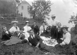 [Group of men and women assembled for a picnic on the lawn in front of the Vancouver Waterworks C...