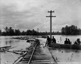 Men in boat on floodwaters at washed out railroad tracks