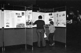 Man and boy viewing the Vancouver City Archives' display, Portholes and Pilings