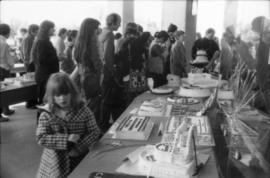 People viewing birthday cakes on display