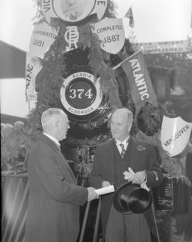 [Mayor Cornett and Charles Cotterell, assistant general manager of the CPR in front of Engine 374...