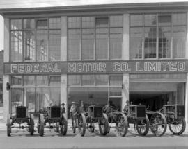 Tractors [lined up in front of the] Federal Motor Co. Limited [building]