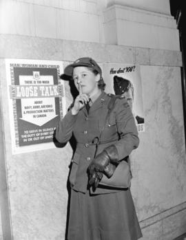 "Private Underhill [C.W.A.C., in front of a ""Loose Talk"" poster]"