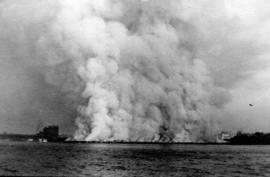 [View from water of the C.N.S.S. dock on fire]