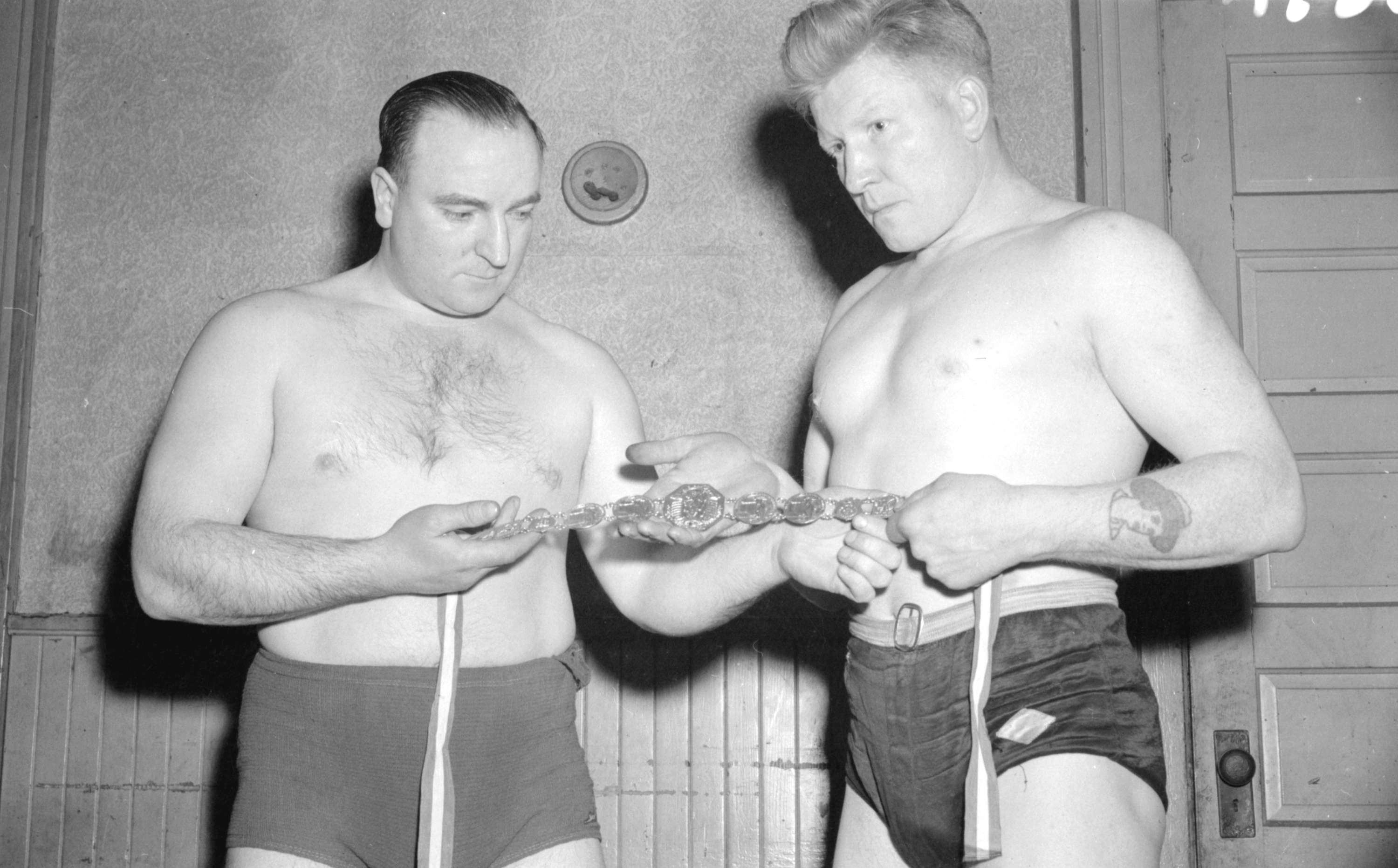 Jack Whalen and Jack Eaton looking at a wrestling belt ...