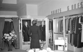 [Woman standing at a full length mirror in the Mademoiselle Ltd. clothing store]