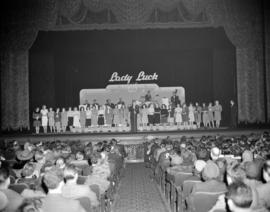 "[Women lined up on the Orpheum Theatre stage at the ""Lady Luck Revue"" awaiting results ..."