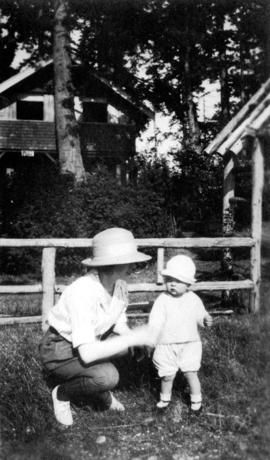 [Woman with small child and cabin in the background at Summit Lake]