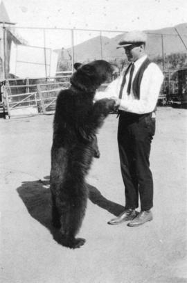 [Ted Taylor standing with a bear in the Metro Pictures Corporation studio lot]