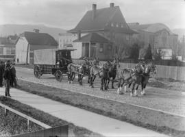 Six horse team pulling a wagon on the street