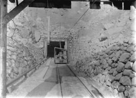 [Machinery on tracks at entrance to partially excavated tunnel for Buntzen Lake Power Plant numbe...