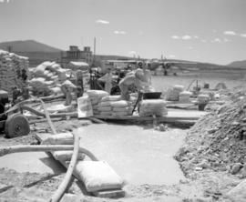 [Crew mixing water with fire control chemicals in large pits for loading into a water bomber at t...