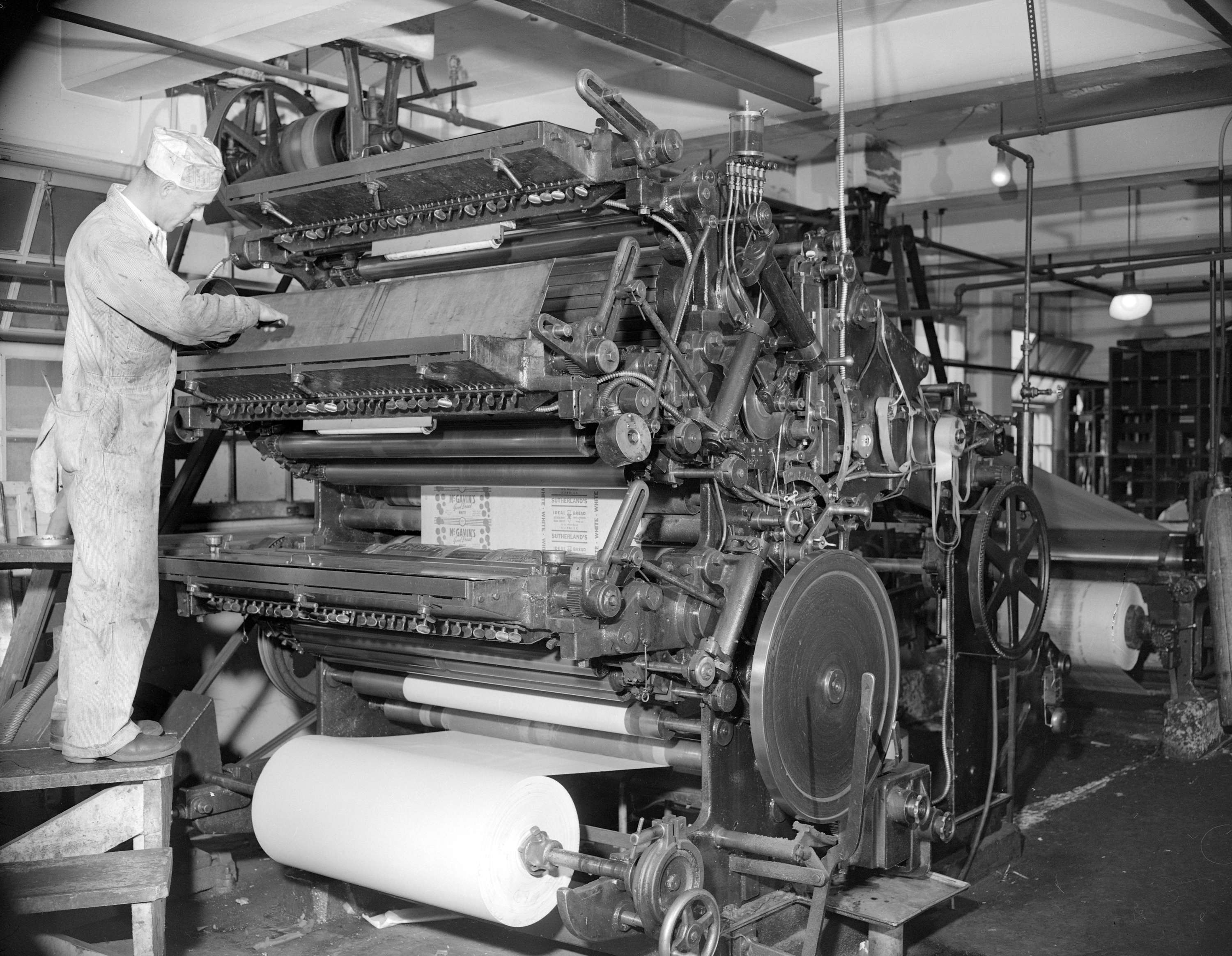 Man at a paper printing machine making wrappers for McGavin's bread