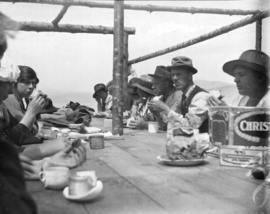[Unidentified group eating a meal outdoors]