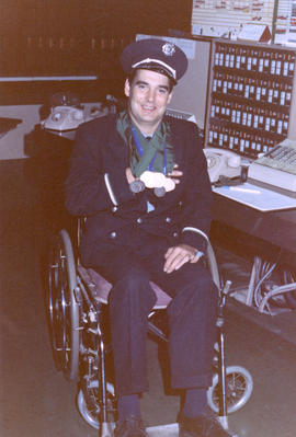 George Shields, fire alarm operator, sitting in wheelchair showing medals from Paraplegic Games