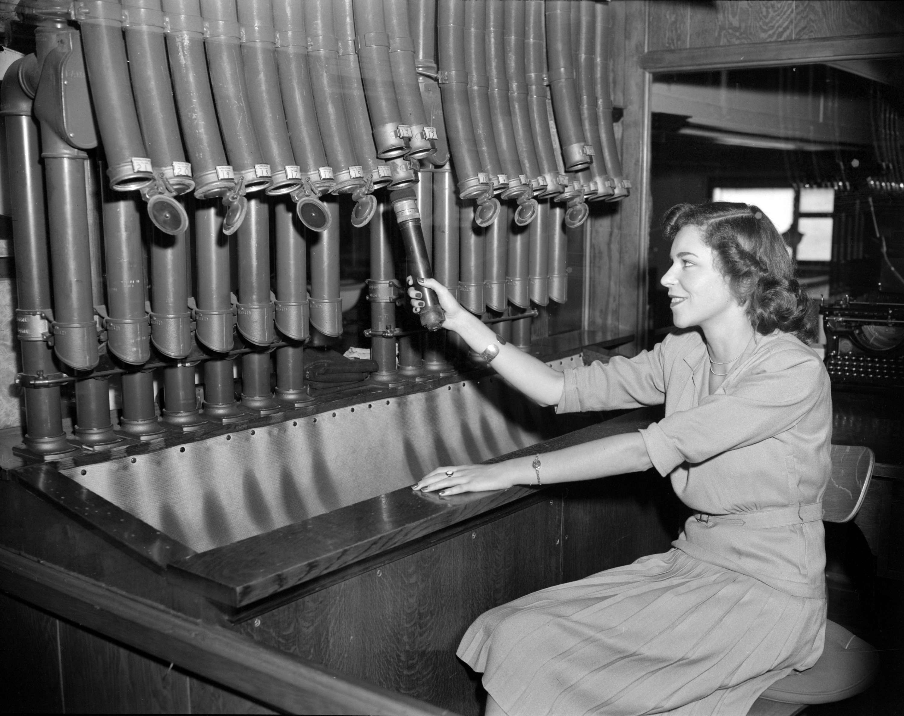 Woman using the pneumatic tube delivery system at