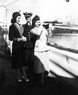 Two Miss P.N.E. contestants with officer aboard the H.M.S. Sheffield