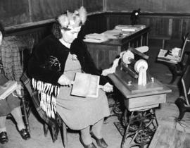 Mrs. Rice, knitting instructor [carding wool at] Nanaimo Indian School