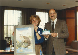Woman holding Centennial otter poster and Mike Harcourt holding a cake
