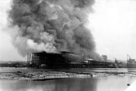 [View from the water of Coughlan's shipyard (gantry) on fire at the foot of Columbia Street ...
