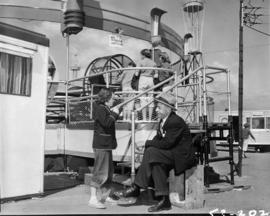 Young girl speaking with man in front of amusement ride in P.N.E. Gayway