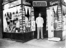 [Unidentified man standing in front of one of the Vancouver Drug Company stores]
