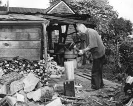 [William Timothy (Tim) Cummings chopping wood behind his home on Park Road near Brockton Point]
