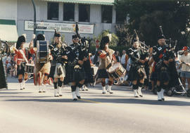 Men in kilts marching in parade with drums and bagpipes