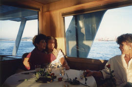 Group seated at indoor table on boat cruise