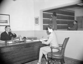 [Woman taking notes while man talks on telephone at Gordon M. Thompson Ltd. offices]
