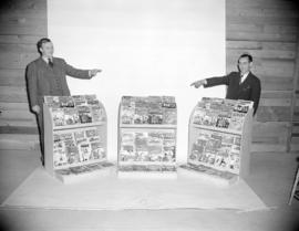 [Two men posing with magazine racks]