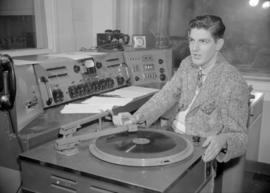 C.K.W.X. radio announcer playing records in the broadcast booth
