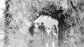 [People passing through the evergreen arch at Stanley Park]