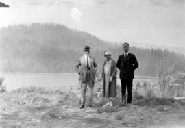[L.D. Taylor, Kate Taylor Cooley and unidentified man standing in front of lake]
