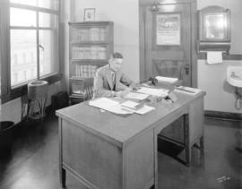 [Portrait of Fred Howlett, Esq. City Clerk at his desk at the temporary City Hall, 16 East Hastin...